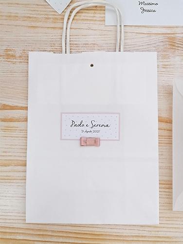BAG - In carta bianca con manici in carta, misure: 16x21x8 cm. Tag personalizzato applicato su un fronte con fiocco piatto semplice.