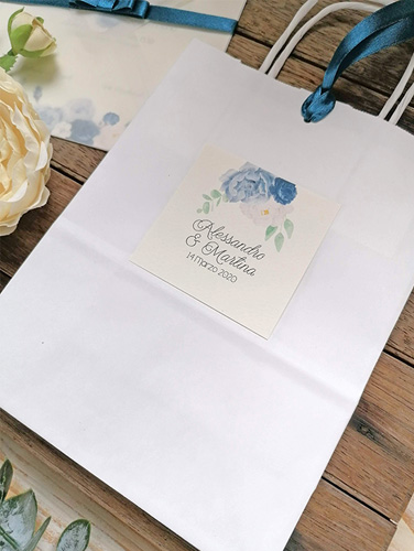 BAG - In carta bianca con manici in carta, misure: 16x21x8 cm. Tag personalizzato applicato su un fronte e foro per chiusura con nastro coordinato.