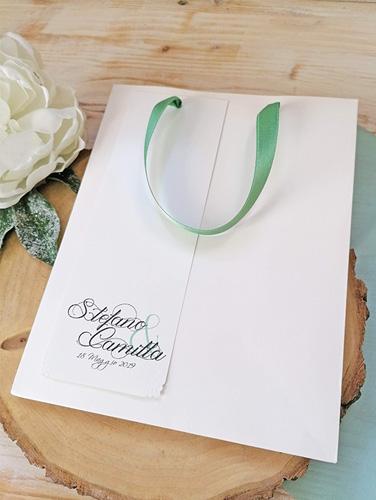 BAG - In carta bianca con manici in doppio raso, misure: 18x23x10 cm. Tag personalizzato applicato su un fronte. Possibilità di aggiungere un foro col nastro per chiusura.