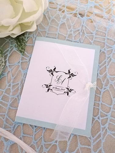 ANNE - Porta salvietta in carta bianca liscia, bordata e crest con iniziali sposi. Nastro in organza. Salvietta rinfrescante confezionata singolarmente inclusa.