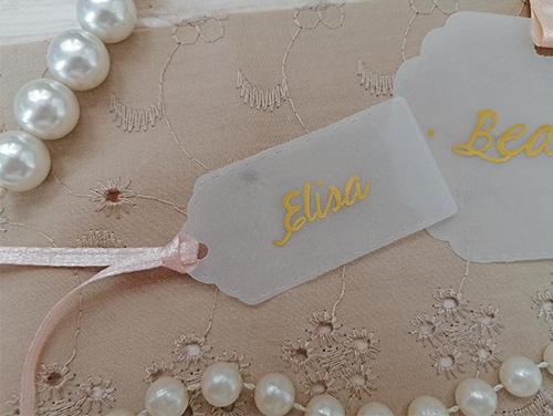 ELISA - Segnaposto, Tag nr 4, misure 5,7x2,8 cm. Nome invitato scritto a mano con penna oro. Foro e nastro decorativo.