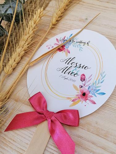 ALICE - Ventaglio in carta liscia bianca, formato ovale. Con bastoncino in legno applicato sul retro. Fiocco semplice applicato. Misure: 10,5x12,5 cm.