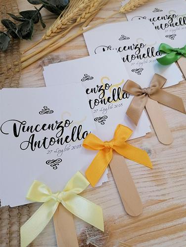 ANTONELLA - Ventaglio in carta liscia bianca, rettangolare verticale, con bastoncino in legno applicato sul retro. Fiocco semplice e angoli intagliati e a rilievo. Misure cartoncino 13x10,5 cm.