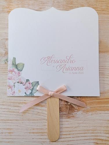 ARIANNA - Ventaglio in carta liscia bianca, sagomato sopra, con bastoncino in legno applicato sul retro. Fiocco semplice. Misure cartoncino 14×14,5 cm.