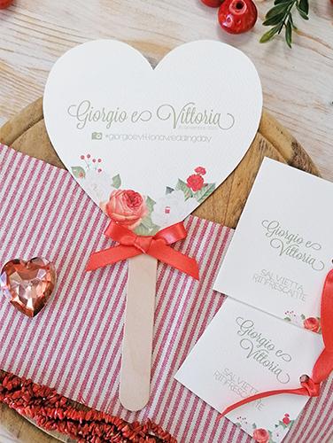 CORALLO - Ventaglio in carta canvas avorio, a forma di cuore, con bastoncino in legno applicato sul retro. Fiocco semplice. Misure cartoncino cuore grande 14,5x14,5 cm.