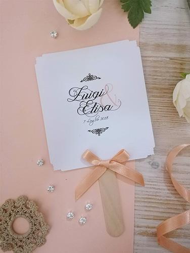 ELISA - Ventaglio in carta liscia bianca, rettangolare verticale, con bastoncino in legno applicato sul retro. Fiocco semplice e angoli intagliati e a rilievo. Misure cartoncino 12x10,5 cm.