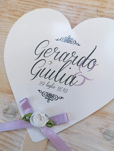 """GIULIA - Ventaglio in carta liscia bianca, a forma di cuore, con bastoncino in legno applicato sul retro. Fiocco semplice e brillantino sulla """"i"""". Misure cartoncino cuore piccolo 10,5x10,5 cm."""