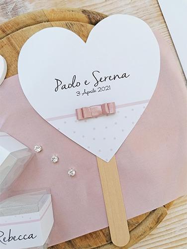 GLICINE - Ventaglio in carta liscia bianca, a forma di cuore, con bastoncino in legno applicato sul retro. Fiocco piatto doppio. Misure cartoncino cuore grande 14,5x14,5 cm.