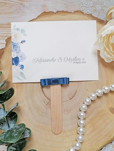 OLTREMARE - Ventaglio in carta canvas avorio, rettangolare orizzontale, con bastoncino in legno applicato sul retro. Fiocco piatto doppio e applicazione di brillantino. Misure cartoncino 10,5x14,5 cm.