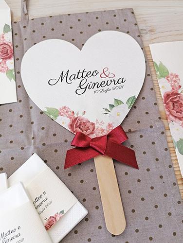 RUBINO - Ventaglio in carta canvas avorio, a forma di cuore, con bastoncino in legno applicato sul retro. Fiocco semplice. Misure cartoncino cuore grande 14,5x14,5 cm.