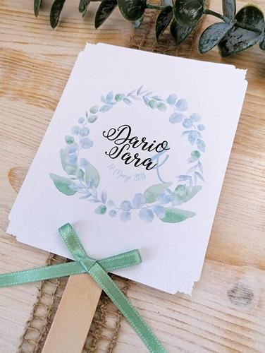 SARA - Ventaglio in carta liscia bianca, rettangolare verticale, con bastoncino in legno applicato sul retro. Fiocco semplice con angoli intagliati e a rilievo. Misure cartoncino 14x10,5 cm.