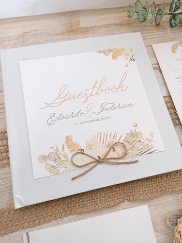 GUESTBOOK - Album con 50 fogli bianchi, 150gr/mtq. Copertina bianca con applicazione personalizzata in carta canvas e fiocco in cordino marrone. Misure: 20,5×20,5 cm.