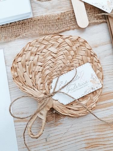 PAMPAS -Ventaglio in foglia di palma intrecciato. Con cordino marrone e tag personalizzato. Misure: 13×14 cm.